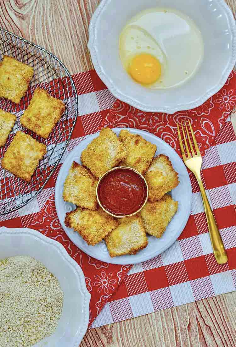 A table set with air fryer ravioli recipe ingredients and a platter of finished ravioli.