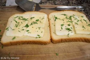The two bread slices topped with butter, garlic powder and chopped parsley.