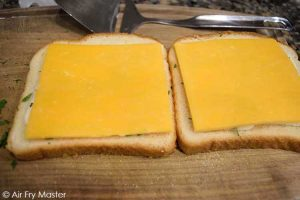 The next layer on the bread slices is the cheese on either side.