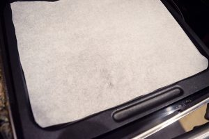 The parchment-lined air fryer tray.