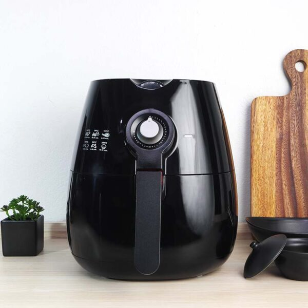 A black basket type air fryer or oil free fryer appliance, mug, dish and cutting board.