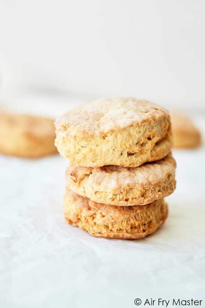 Can You Bake In An Air Fryer? Three air fryer biscuits stacked up on a white background.