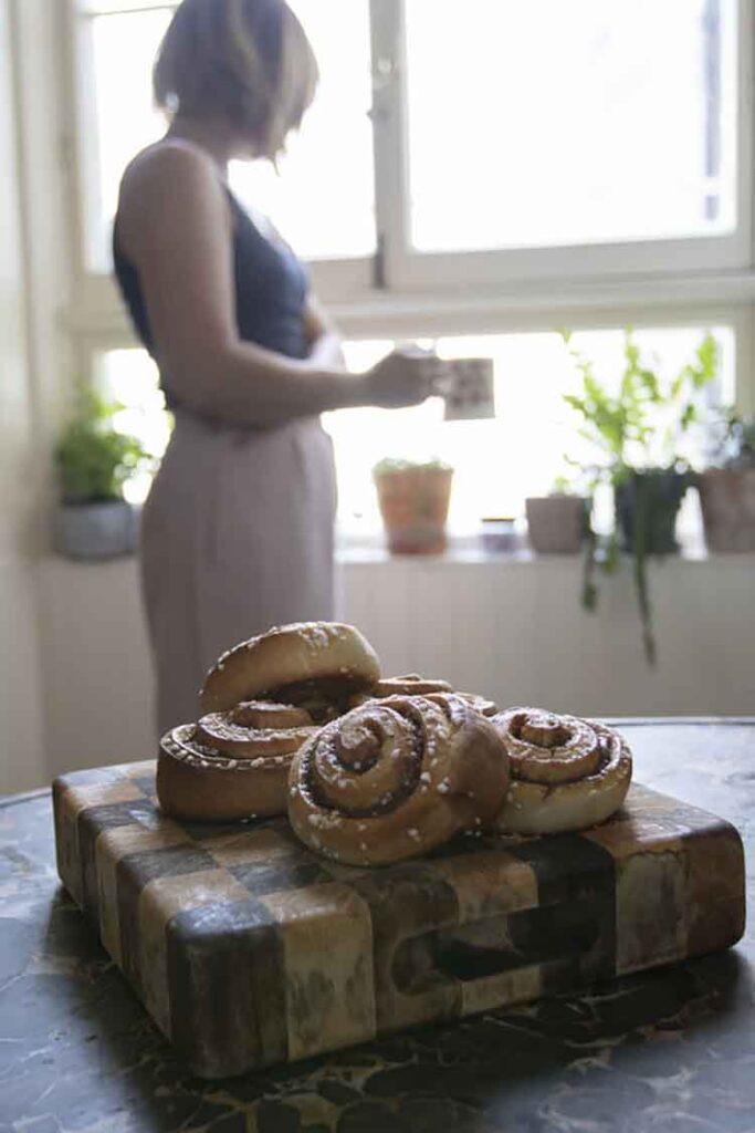 Can You Bake In An Air Fryer? A stack of freshly baked cinnamon rolls resting on a cutting board.