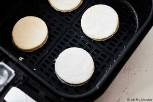 Air fryer biscuits sitting in the air fryer basket, ready to be baked.