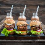 Air fryer meatloaf sliders sit lined up on a plate.