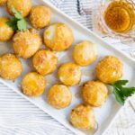 Keto air fryer caramel goat cheese balls sit lined up on a platter with some fresh greens between them for garnish.